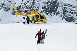 Heli-skiers arrive at yellow helicopter